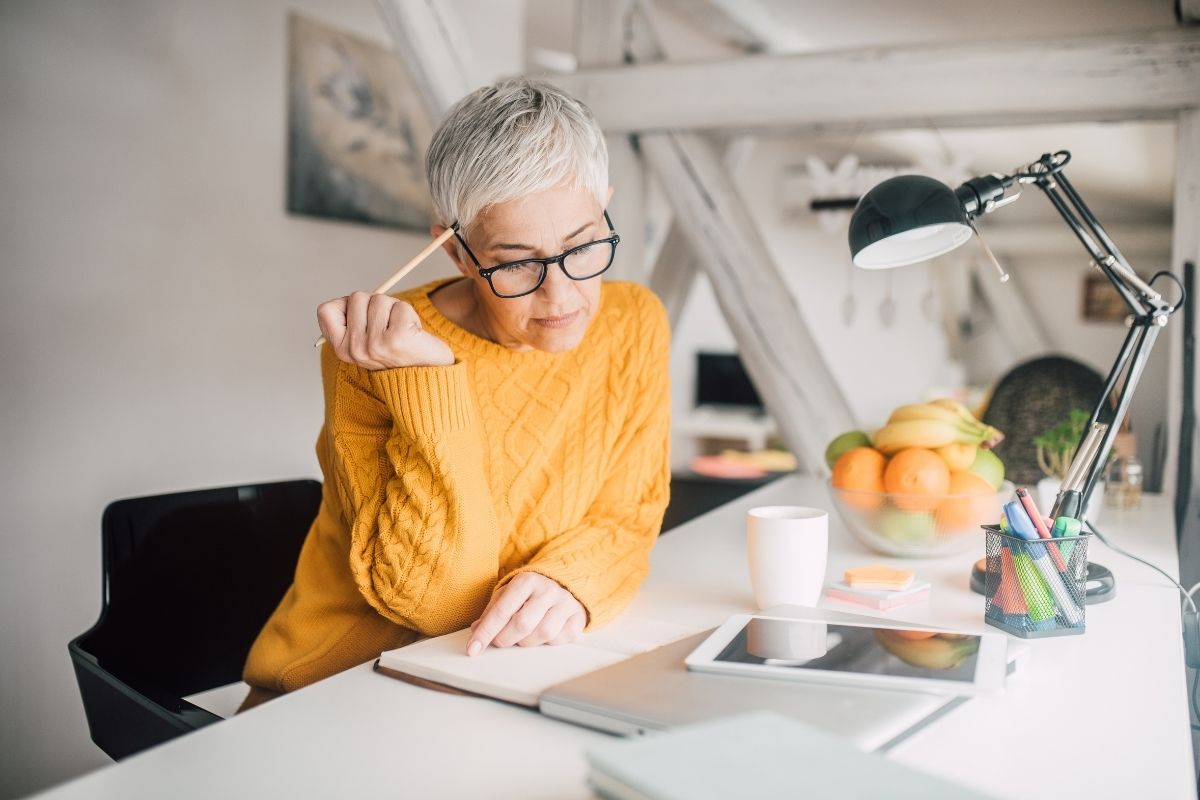 Older woman working with reasons to postpone retirement