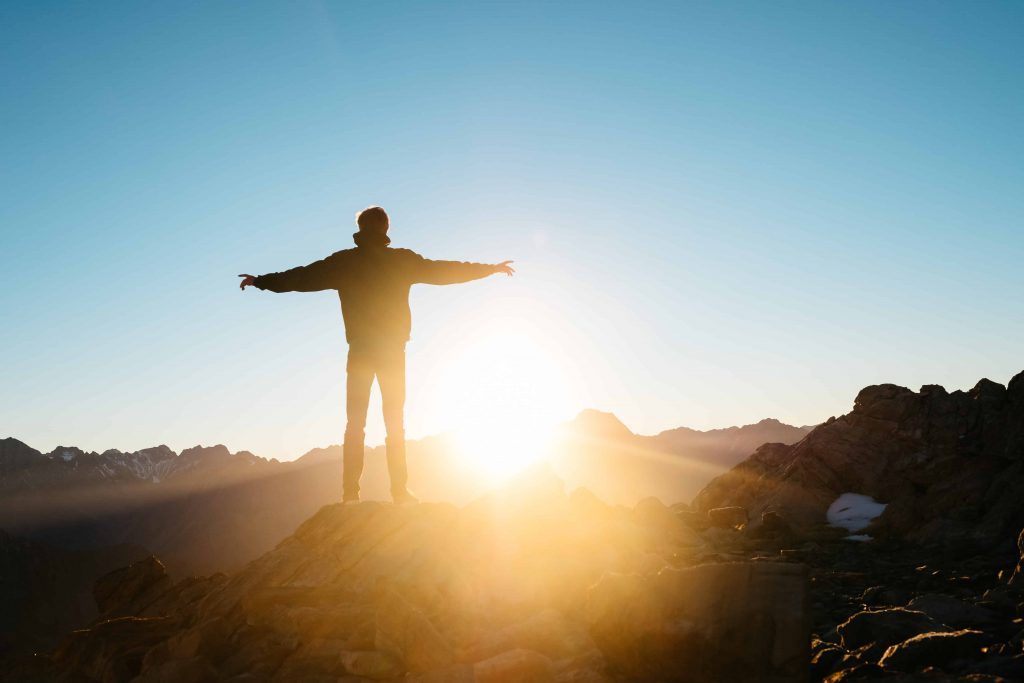 person at top of mountain at sunrise representing persistence