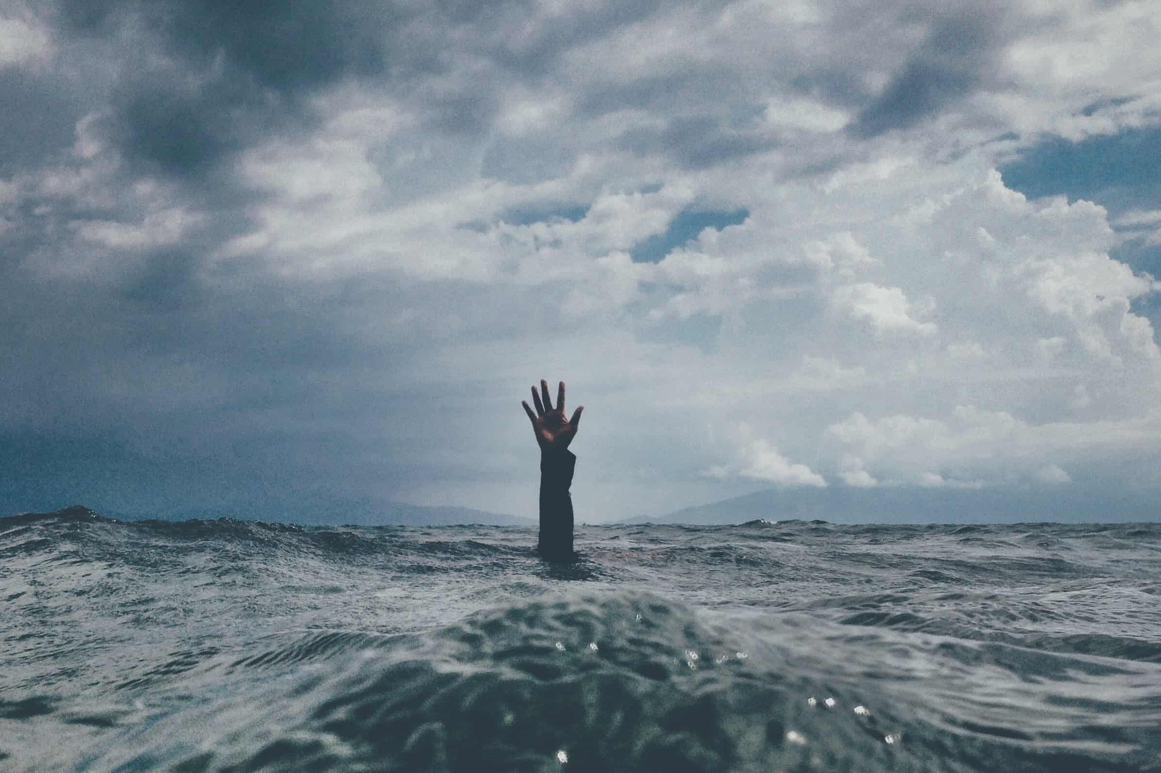 A hand coming out of the water, signifying how our mental health is affected by financial stress
