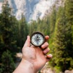 hand holding compass representing finding direction in life