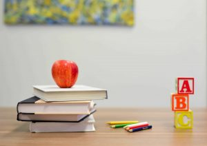 stack of books with apple on desk