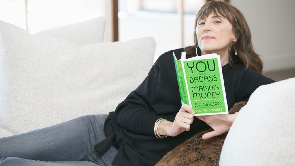 author holding You Are A Badass At Making Money book