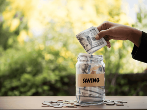 Hand putting money in saving jar representing good money habits