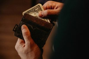 Man pulling cash from wallet representing frugal vs cheap