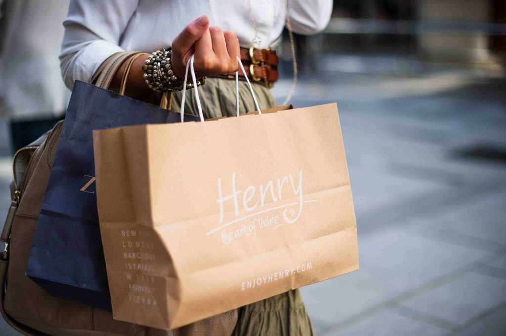 Woman with shopping bags trying to stop spending money
