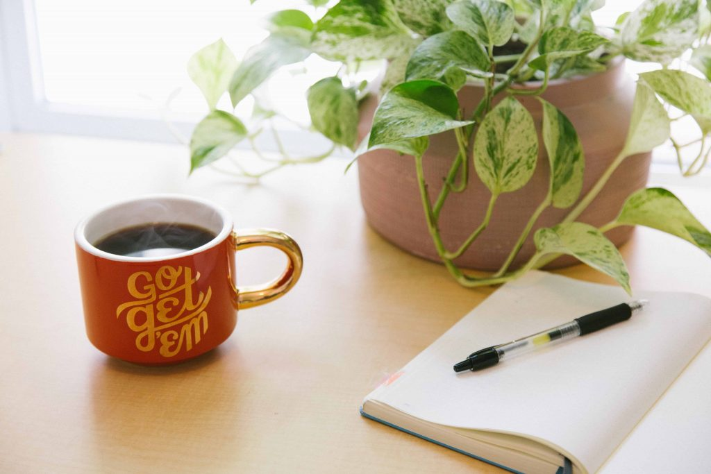 Coffee, plant, and notebook on desk for retirement planning for late starters