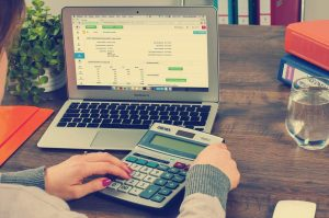 Woman on calculator looking for ways to save money on a tight budget
