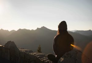 Woman on mountain pondering the willingness to change