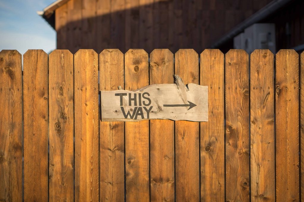 Wood fence with sign This Way representing direction to wealth creation