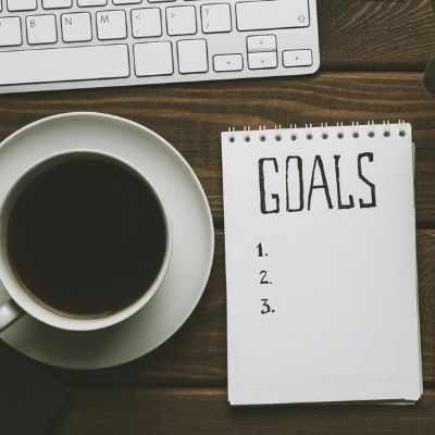 Coffee and notepad for goals