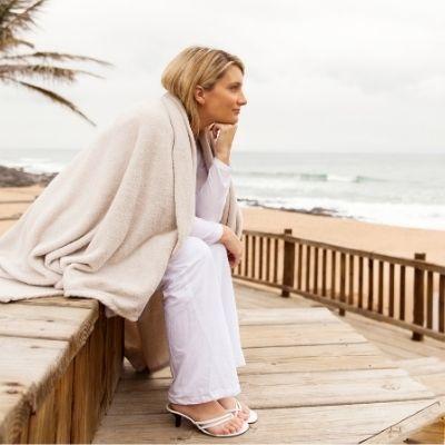Woman thinking next to ocean