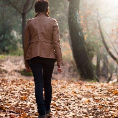 Woman walking through woods