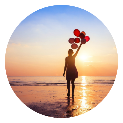 Woman with balloons on beach