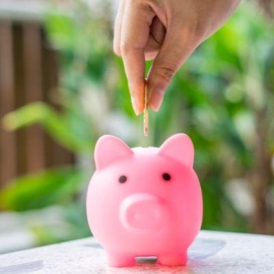 Woman putting a coin in a piggy bank