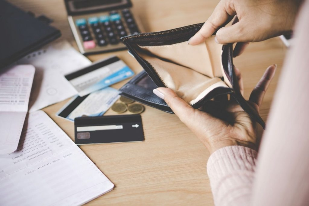 Woman with empty wallet learning how to save money when you're broke