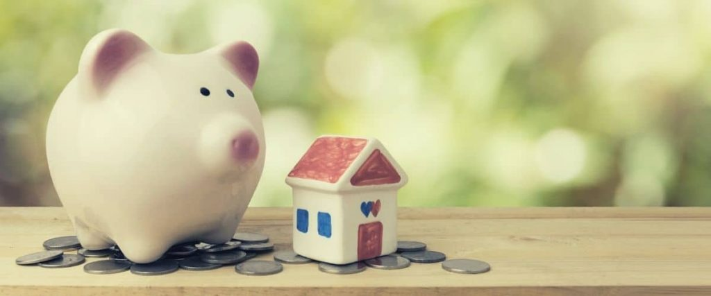 Piggy bank, small ceramic house, and coins on table