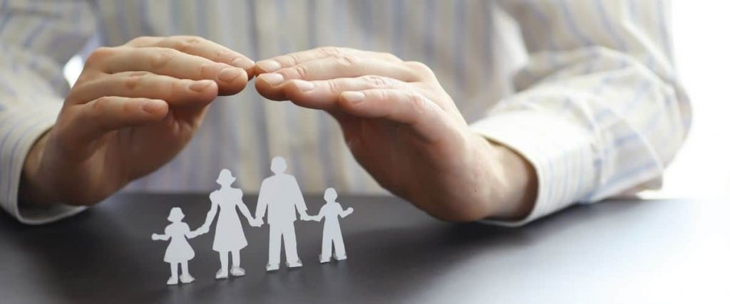 Hands placed over a paper cutout of a family