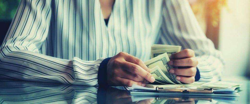 Woman counting $100 bills