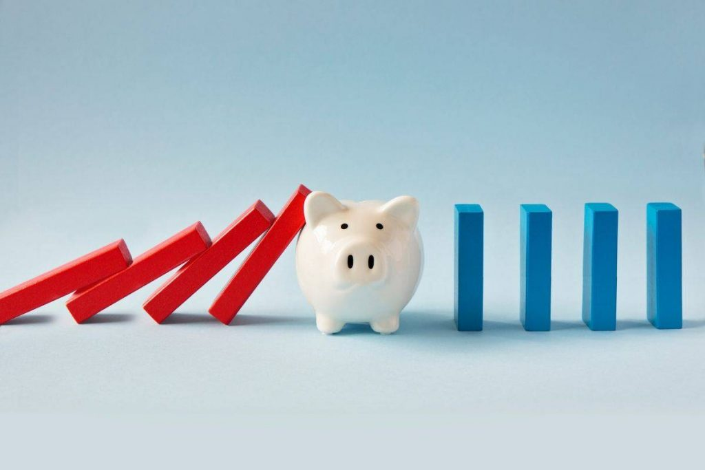 Piggy bank with dominoes representing financially sound