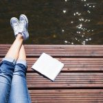 Woman next to lake writing a stress management plan