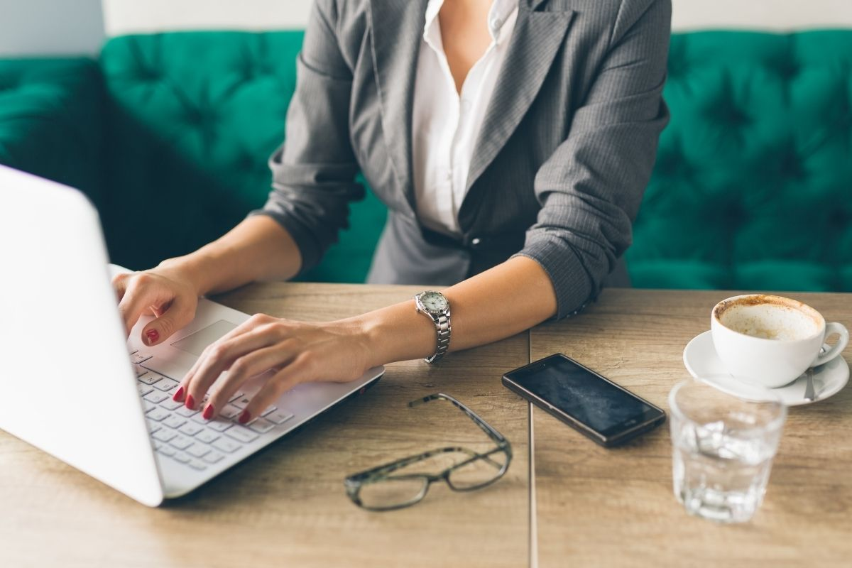 Woman on laptop looking for ways to make extra money with a side hustle